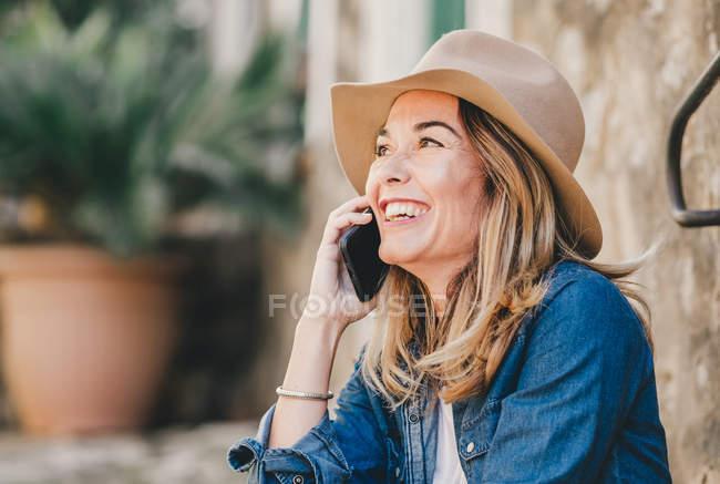 Вид сбоку улыбающейся молодой женщины, говорящей по мобильному телефону и сидящей на каменной лестнице снаружи — стоковое фото