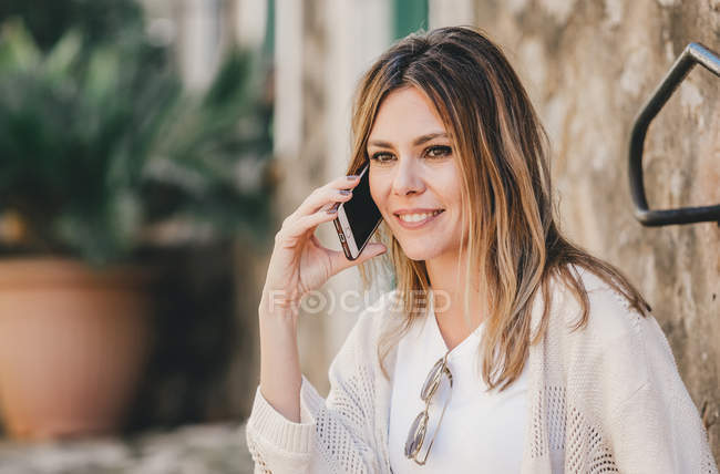 Smiling woman talking on mobile phone and sitting on stone stairs outside — Stock Photo