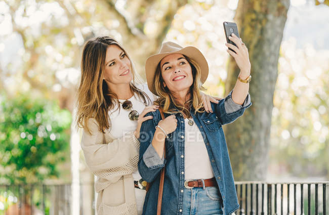 Young attractive girlfriends smiling and taking selfie in beautiful place with green plants in street — Stock Photo