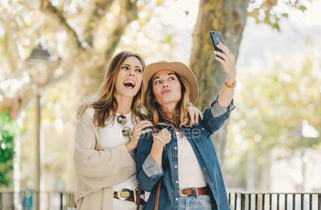 Jovens namoradas atraentes sorrindo e tomando selfie no lugar bonito com plantas verdes na rua — Fotografia de Stock