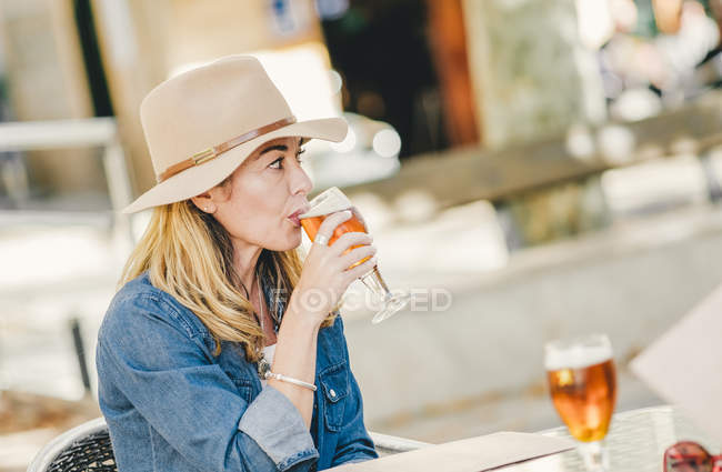 Attractive stylish woman with glass of refreshing beer sitting in cafe and looking away — Stock Photo