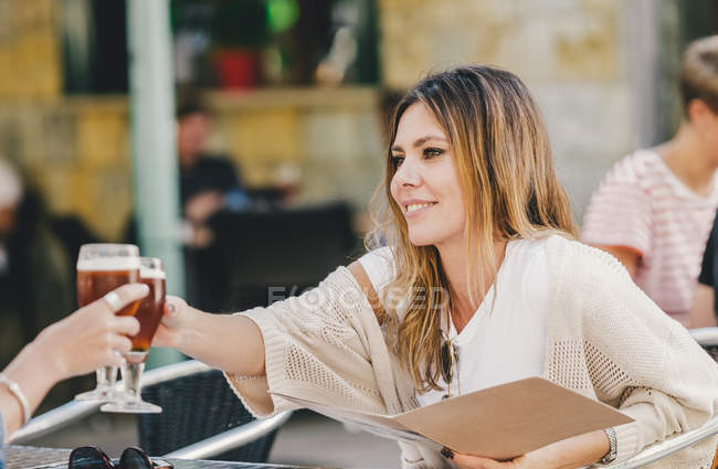 Attractive stylish woman with glass of refreshing beer sitting in cafe and clinking with friend — стокове фото