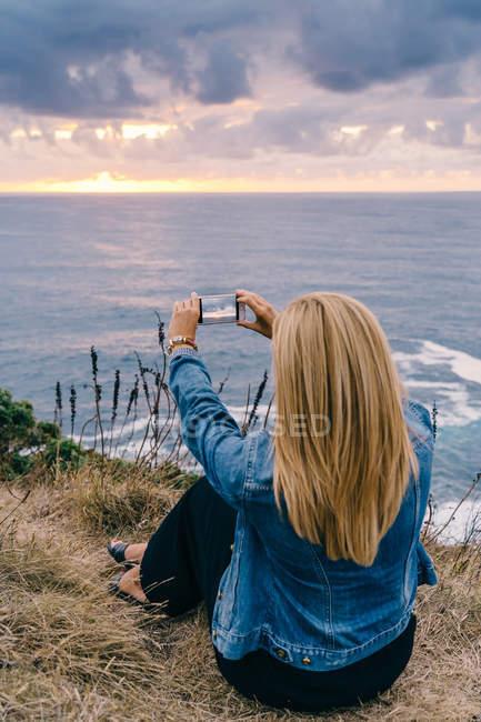 Vista posteriore della donna che scatta foto di maestoso tramonto pittoresco paesaggio marino — Foto stock