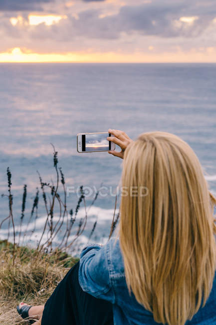 Обратный вид женщины, фотографирующей величественный закат живописный морской пейзаж — стоковое фото