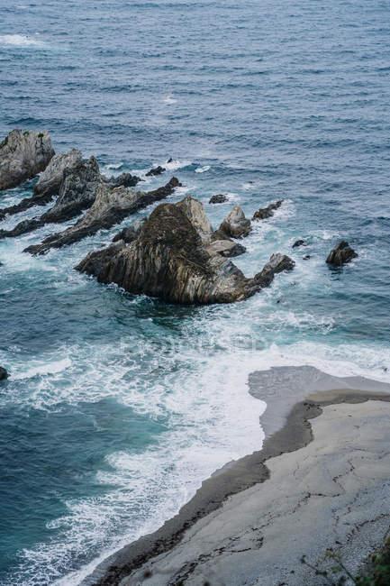 Picchi rocciosi circondati da acqua schiumosa nelle giornate ventose — Foto stock