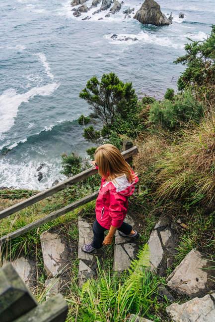 Woman walking down on stone steps leading down to foamy sea — Stock Photo
