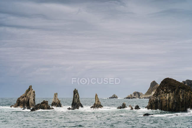 Rocky peaks protrude from water in cloudy day — Stock Photo