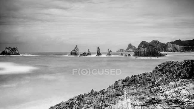 Скелясті вершини випинаються з води в похмурий день. — стокове фото