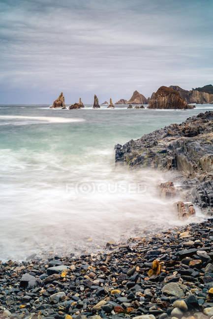 Les pics rocheux sortent de l'eau par temps nuageux — Photo de stock