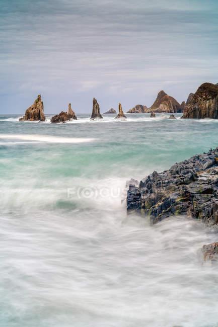 Picchi rocciosi sporgono dall'acqua nelle giornate nuvolose — Foto stock