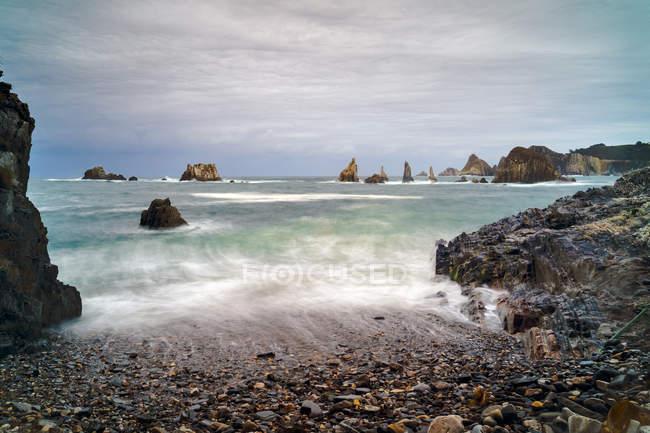Picos rocosos sobresalen del agua en el día nublado - foto de stock