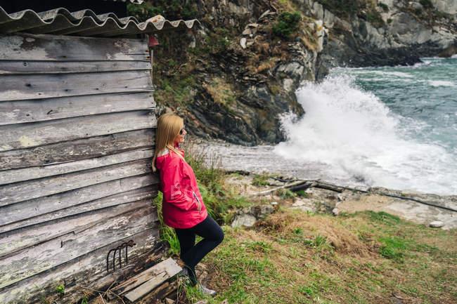 Vista lateral da mulher pensativa em capa de chuva vermelha apoiada em paredes de madeira da velha casa à beira-mar lavada por ondas espumosas de mar — Fotografia de Stock