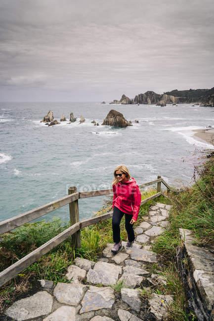 Mujer subiendo escaleras que vienen de la orilla del mar - foto de stock