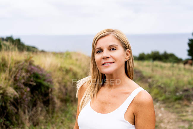 Inspired blonde woman with charming smile looking at camera while enjoying of views of countryside around — Stock Photo