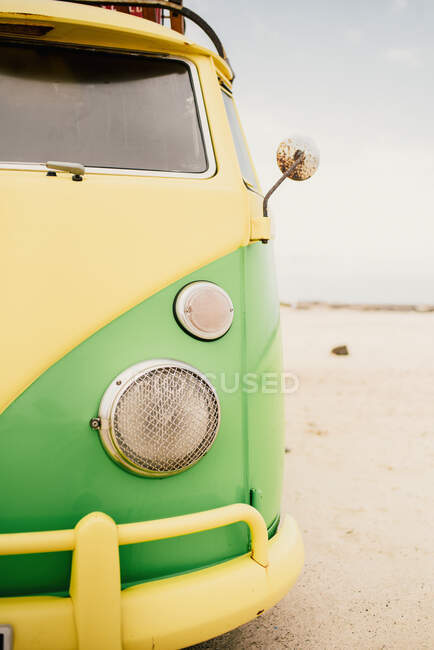 Part on front view of retro minibus with round headlights colored in green and yellow paints parked on sandy beach — Stock Photo