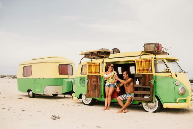 Amigos en minibús con remolque en la playa - foto de stock