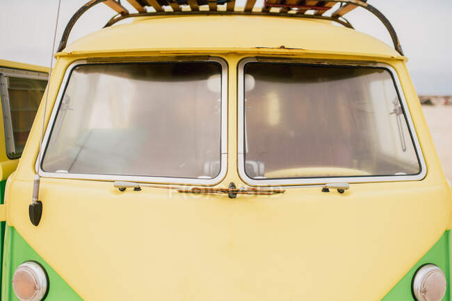 Bright retro minibus with round headlights on beach — Stock Photo