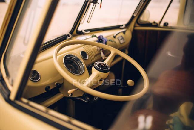 Водіння колеса ретро-жовтого автомобіля в порожній кабіні через скло — стокове фото