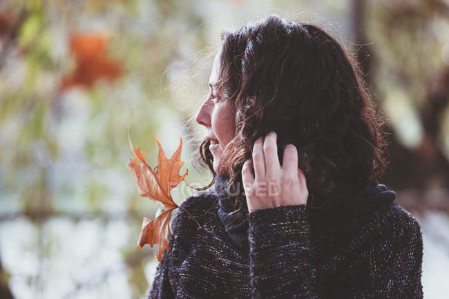 Woman with curly hair looking away on blurred background of peaceful autumn park — Stock Photo