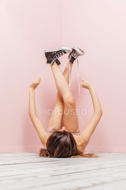 Woman's aesthetic legs looking up on pink background — Stock Photo