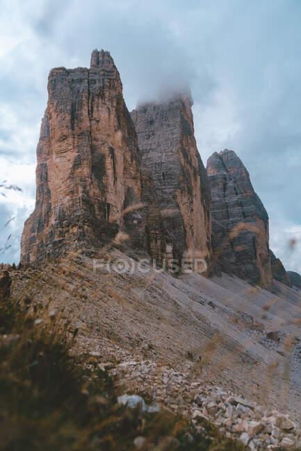 Vue imprenable depuis les contreforts avec de l'herbe verte et de petits rochers de sommets brumeux de montagnes Drei Zinnen dans les Dolomites par temps couvert — Photo de stock