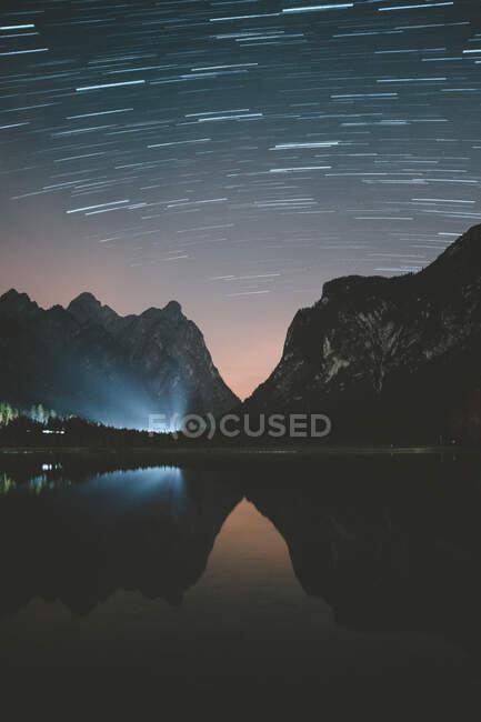 Блакитні промені світла, що сяють у прекрасну спокійну ніч з ясним зоряним небом на озері в Доломітах під час гарної погоди. — стокове фото