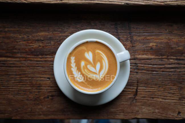 De arriba taza de capuchino fresco con forma de corazón en espuma servido en la mesa de madera en la cafetería - foto de stock