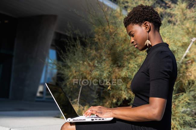 Vista lateral de la mujer afroamericana concentrada en vestido negro elegante usando el ordenador portátil en la calle - foto de stock