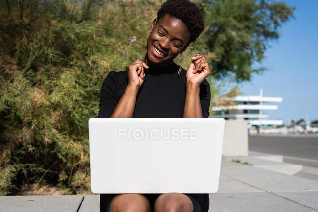 Allegro donna eccitata in elegante abito nero utilizzando il computer portatile sul marciapiede sulla strada — Foto stock