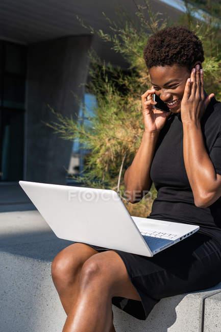 Афроамериканка в элегантном черном платье с ноутбуком и разговаривая по мобильному телефону на улице — стоковое фото