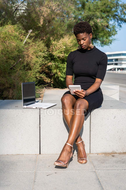 Concentrated African American woman in elegant black dress using mobile phone near laptop while relaxing on pavement — Stock Photo