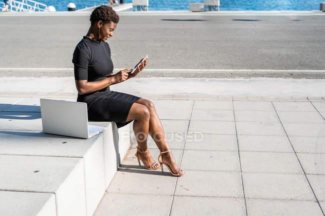 Вид з боку концентрованих афро-американської жінки в елегантній чорній сукні за допомогою мобільного телефону, сидячи на тротуарі — стокове фото