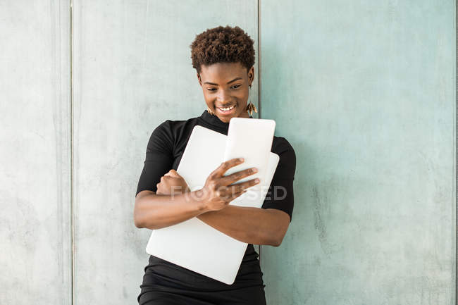 Крутая афроамериканская умная женщина делает селфи, держа ноутбук, стоящий на бетонной стене — стоковое фото