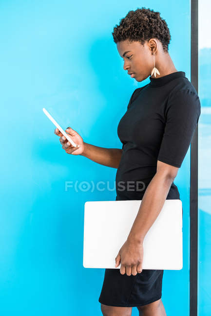 Cool African American smart woman using mobile phone holding laptop while standing on blue background — Stock Photo