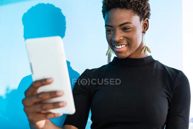 Cool mujer inteligente afroamericana tomando selfie sobre fondo azul - foto de stock