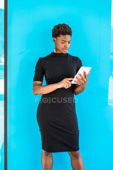 Cool mujer inteligente afroamericana usando un teléfono móvil mientras está de pie sobre fondo azul - foto de stock