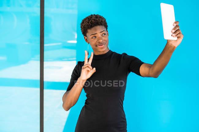 Cool donna afro-americana intelligente prendendo selfie e mostrando segno v su sfondo blu — Foto stock