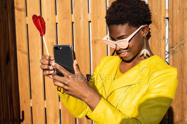 Mulher afro-americana na moda desfrutando pirulito por cerca de madeira tirando selfie com telefone celular — Fotografia de Stock