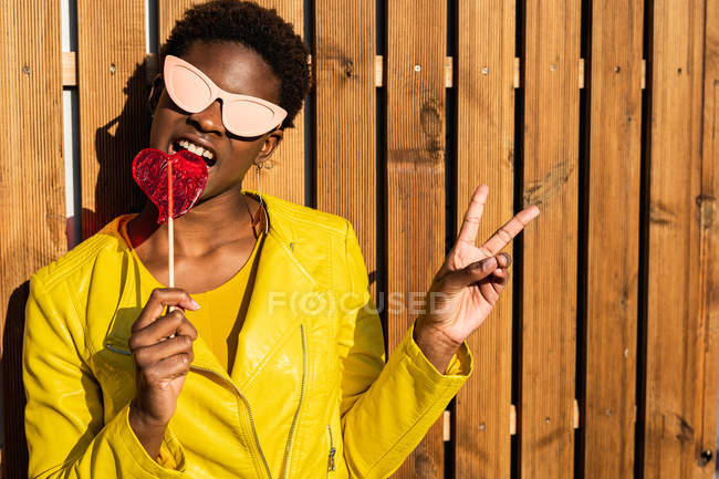 Trendy African American woman enjoying heart shaped lollipop by wooden fence and gesturing peace sign — Stock Photo