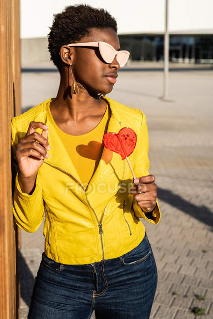 Trendy African American woman in sunglasses in yellow jacket enjoying heart shaped lollipop by wooden fence — Stock Photo