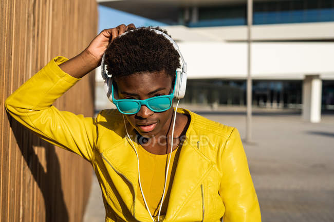 African American woman in stylish bright jacket and bright blue sunglasses using headphones standing near a modern building — Stock Photo