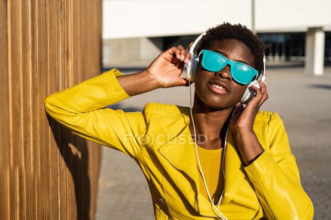 Femme afro-américaine dans une veste lumineuse élégante et des lunettes de soleil bleu vif à l'aide d'écouteurs debout près d'un bâtiment moderne — Photo de stock