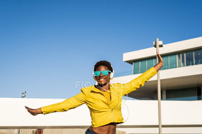 Low angle of happy African American woman in stylish bright jacket and sunglasses jumping with hands up — Stock Photo