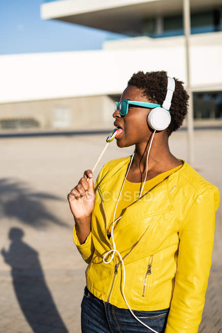 Афроамериканка в солнцезащитных очках в желтой куртке наслаждается леденец и слушает музыку в наушниках — стоковое фото