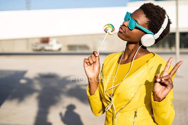 Femme afro-américaine en lunettes de soleil en veste jaune profitant d'une sucette et écoutant de la musique sur écouteurs — Photo de stock