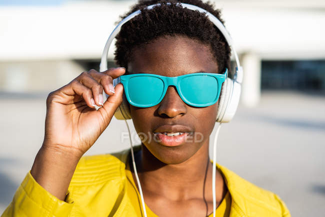 Mulher afro-americana em elegante casaco brilhante e óculos de sol azul brilhante usando fones de ouvido em pé perto de um edifício moderno — Fotografia de Stock