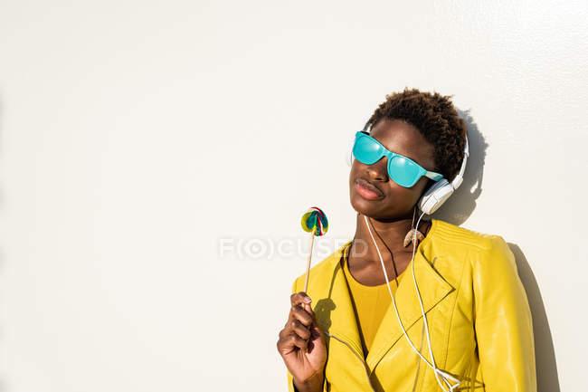 Mulher afro-americana em óculos de sol em casaco amarelo desfrutando de um pirulito e ouvindo música em fones de ouvido — Fotografia de Stock