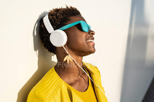 Афроамериканець жінка в стильному яскравий Жакет і яскраво-сині сонцезахисні окуляри, використовуючи навушники спираючись в білу стіну — стокове фото