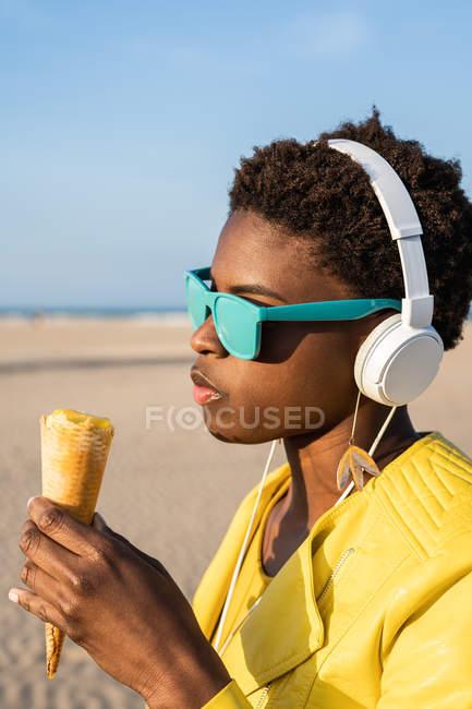 Vista lateral da mulher afro-americana na moda em casaco amarelo brilhante desfrutando de sorvete em pé na praia arenosa — Fotografia de Stock