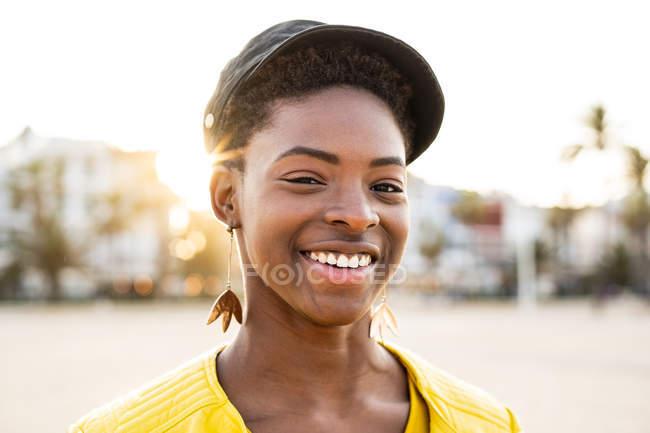 Portrait de femme afro-américaine heureuse en veste lumineuse élégante regardant à la caméra sur fond flou plage de sable — Photo de stock